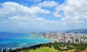 Image of Honolulu skyline. Follow these Space-A flying tips and consider flying through Alaska instead.