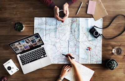 Image of couple with laptop and map planning travel using military travel blogs