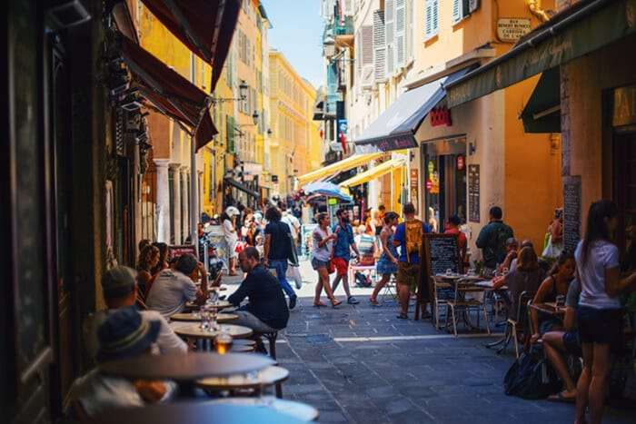 Picture of a busy pedestrian street with people sitting in cafes