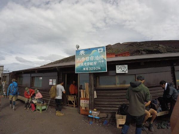 Hikers at a rest stop while climbing Mount Fuji