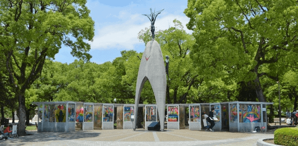 Stone monument to children with colorful paintings in the background, Hiroshima Memorial Park