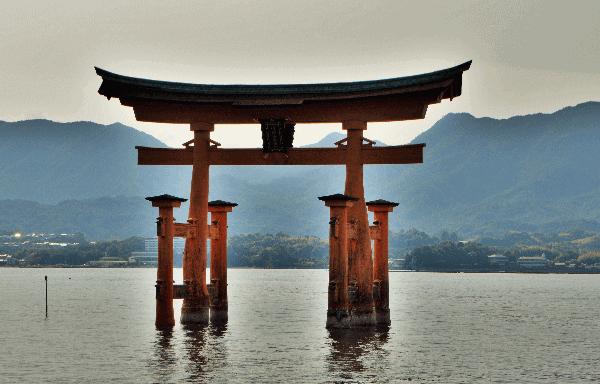 Picture of the orange Torii gate with the sun setting behind it on Miyajima Island