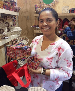 A smiling woman holding baskets in Medellin, Colombia